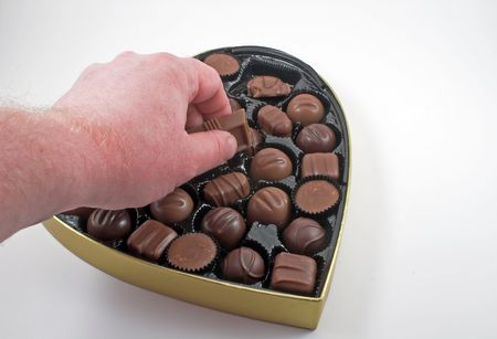 Reaching in to a box of chocolate Valentine candy. Imagens