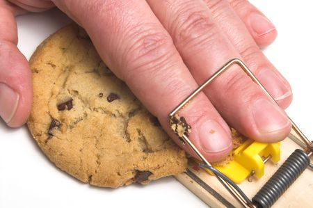 baited: A hand caught in a mousetrap. Dieting concept. Stock Photo