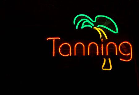 salon and spa: A neon light tanning shop sign on the front of a store.