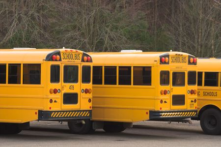 A row of school buses in a parking lot. Stock Photo - 2553418