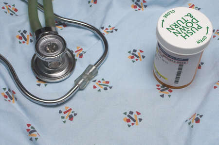 nursing bottle: A medical gown, stethoscope and bottle of pills. Stock Photo