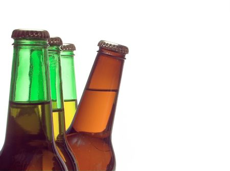 A delicious cold beer peeking from behind green bottles. Stock Photo - 2567856