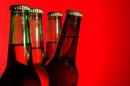 near beer: A delicious cold beer peeking from behind green bottles.