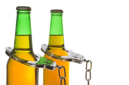 Drunk driving concept - bottled beer and handcuffs. photo