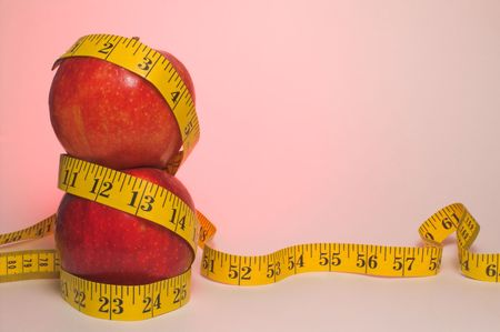 Two red apples wrapped in a tailor's measuring tape. Stock Photo - 2614810