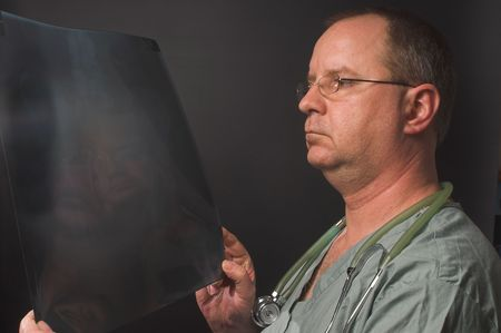 A radiologist looking at a patients x-ray. photo