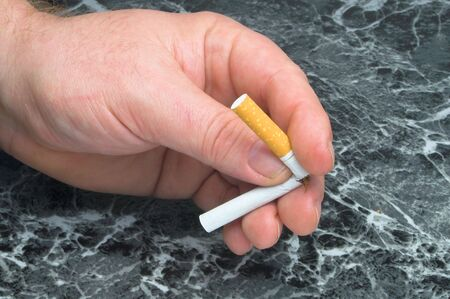 quitting: A person breaking a cigarette, signifying that they are quitting smoking.