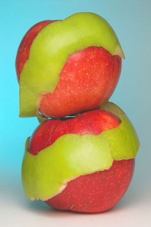 granny smith apple: Two red apples wrapped in a Granny Smith apple peel.