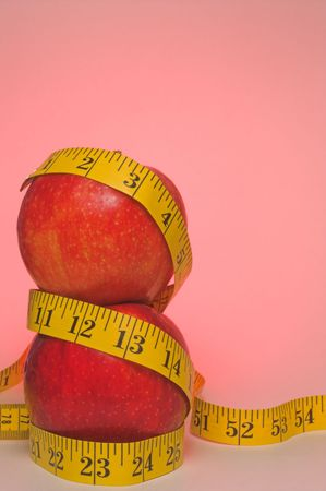 Two red apples wrapped in a tailor's measuring tape. Stock Photo - 2632264