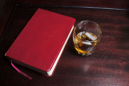 passages: A glass of bourbon on the rocks next to a bible. Stock Photo
