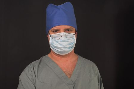 A medical doctor dressed in scrubs performing surgery. Stock Photo - 2649970