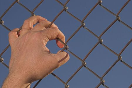 A person attempting an escape over a chain link fence.