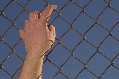 detained: Una persona que intenta escapar de una cadena de m�s de un enlace valla.  Foto de archivo