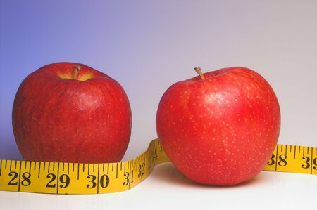 newyears: Two red apples wrapped in a tailors measuring tape. Stock Photo