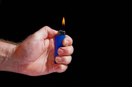 gas lighter: A person lighting a disposable butane lighter.