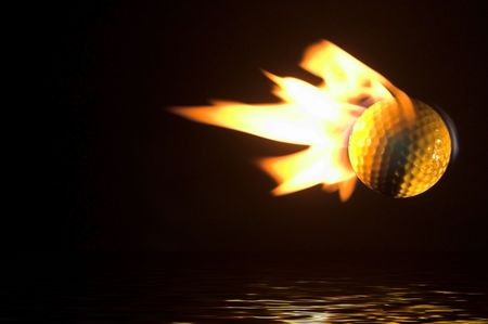A flaming golf ball flying over a water hazard. photo