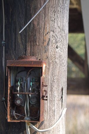 An old electrical box on a telephone pole.