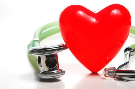 A red heart shape and a medical stethoscope. photo