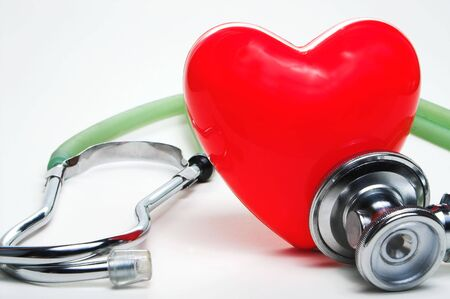 cardiac care: A red heart shape and a medical stethoscope.