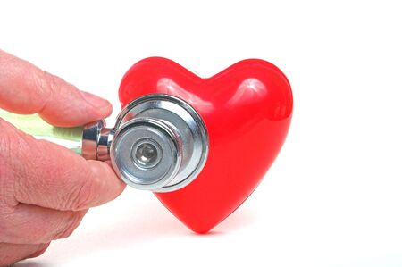 enfermedades del corazon: Una forma de coraz�n rojo y un estetoscopio m�dico.  Foto de archivo