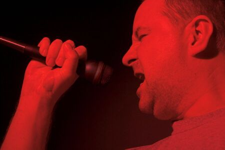 wail: A male singer performing live on stage. Stock Photo