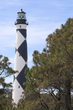 guiding: A historic lighthouse guiding ships away from rocky shoals.