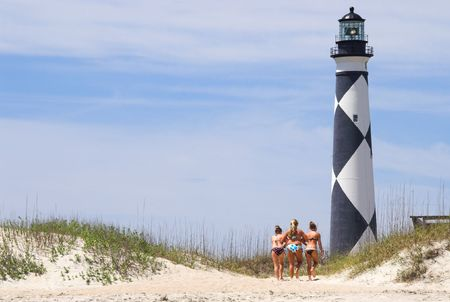 Three sunbathers walking towards a historic lighthouse. photo