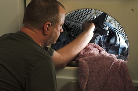 A man taking laundry out of a clothes dryer. Stock Photo - 2933173