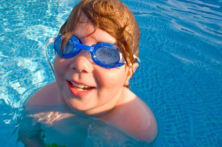 A little boy resting on the edge of a pool. Stock Photo - 3096104