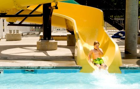 A young boy sliding down a water slide. Stock Photo