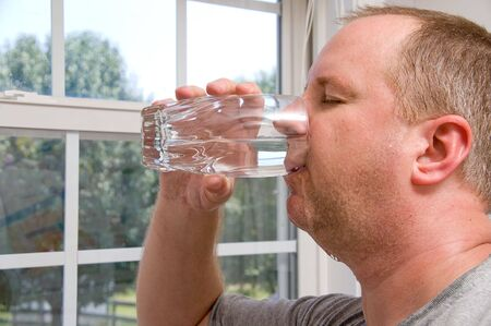 quencher: A man drinking a glass of water. Stock Photo
