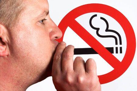 prohibido fumar: Un hombre fumando un signo para no fumadores