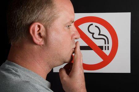 anti tobacco: A man smoking a no smoking sign.
