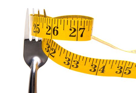 newyears: A tailors measuring tape on a dinner fork. Stock Photo