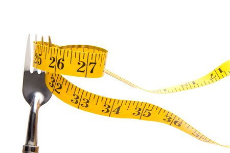 eat right: A tailors measuring tape on a dinner fork. Stock Photo