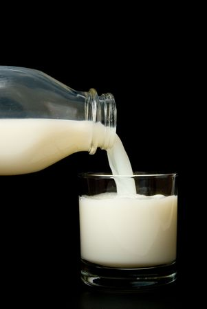 Pouring milk into a glass ready for consumption. Stock Photo - 3588138