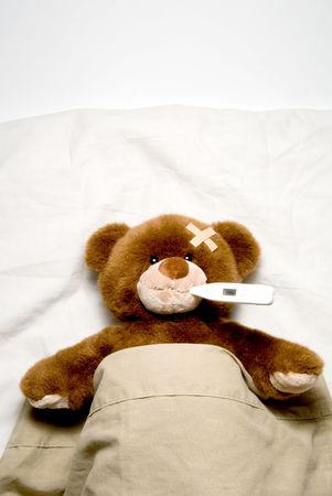 sick person: A very Sick Teddy Bear laying in his bed.