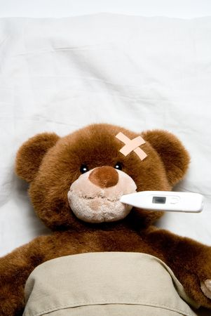 pediatric: A very Sick Teddy Bear laying in a bed.