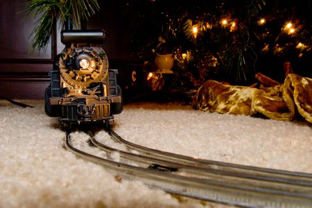 A model train making its way around a Christmas tree.