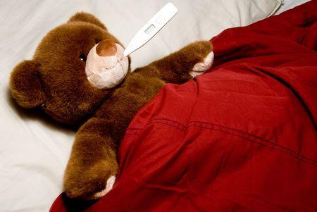 A sick teddy bear taking its temperature.