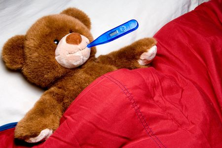 A sick teddy bear with a thermometer in his mouth. photo