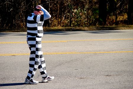 An escaped convict discreetly hiding in the middle of the road. Stock Photo - 3989544