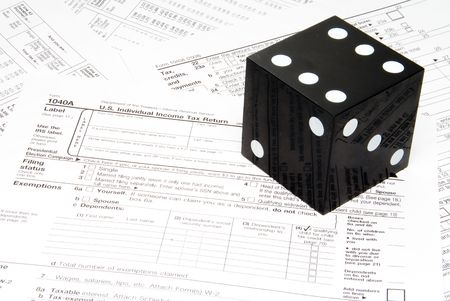 high stakes: A giant die on a stack of tax forms. Stock Photo