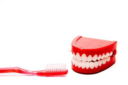 A toothbrush and a set of chattering teeth in a glass. photo