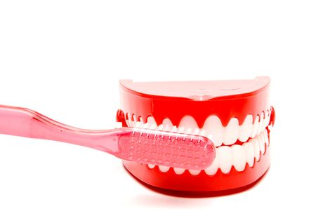 A toothbrush and set of chattering teeth in a glass. photo
