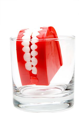 disinfecting: A set of chattering teeth in a glass. Stock Photo