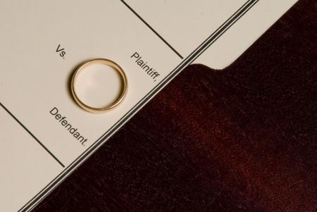 A folder for a divorce case with a wedding ring. photo