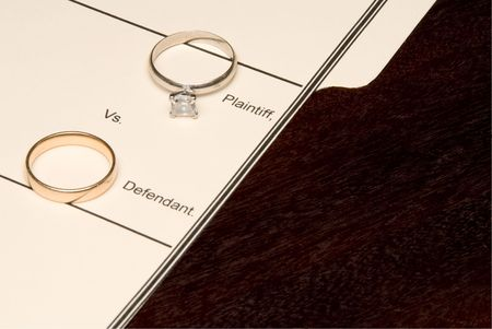 A folder for a divorce case and wedding rings.