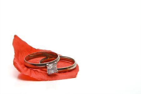 A diamond wedding ring on a fake rose petal. photo