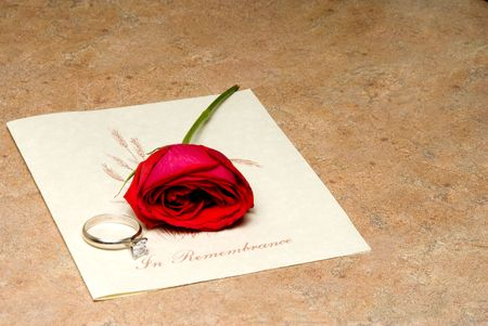 pass away: A funeral program with a rose and wedding ring.